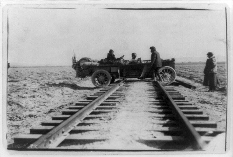 car straddling railroad