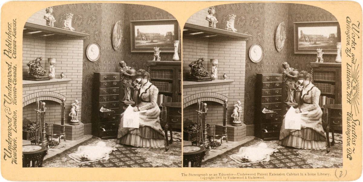 stereograph of a woman looking at a stereograph