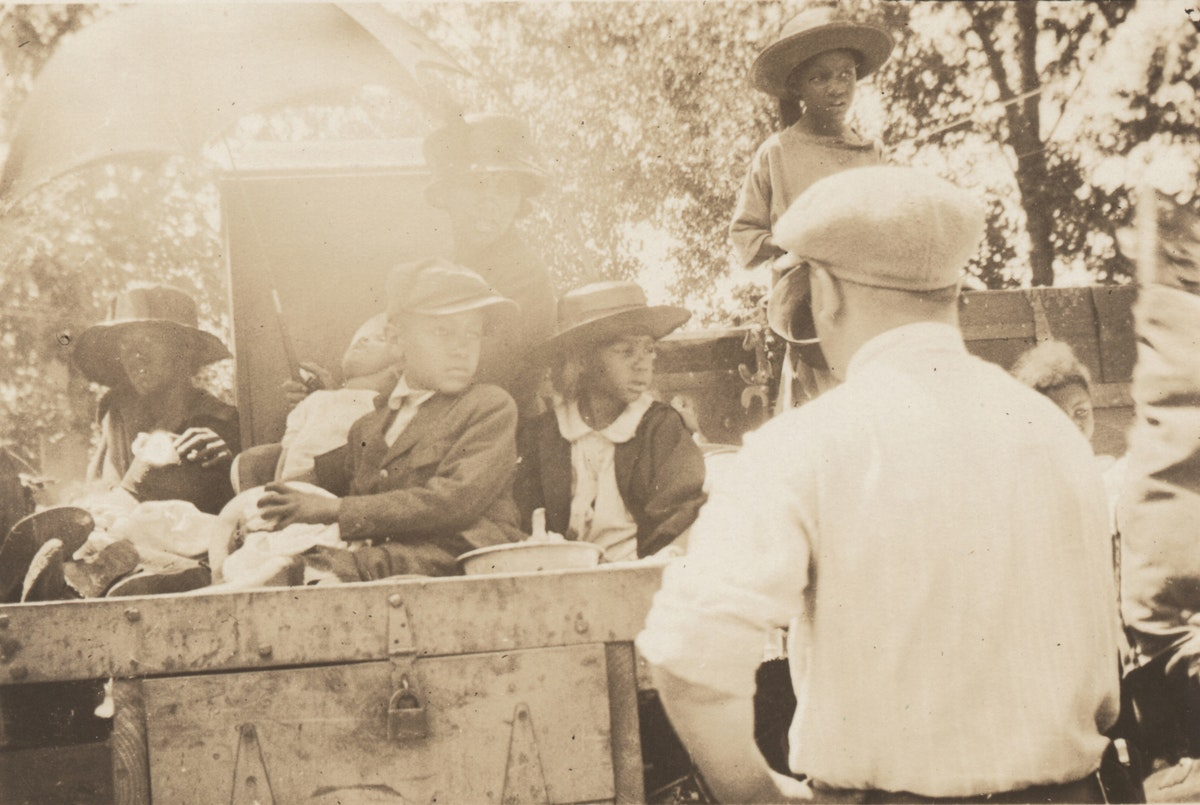 Black woman and children seated in wagon and watched over by white man