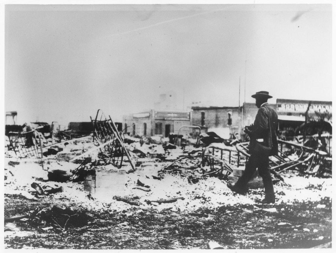 Man walking through rubble, tulsa massacre
