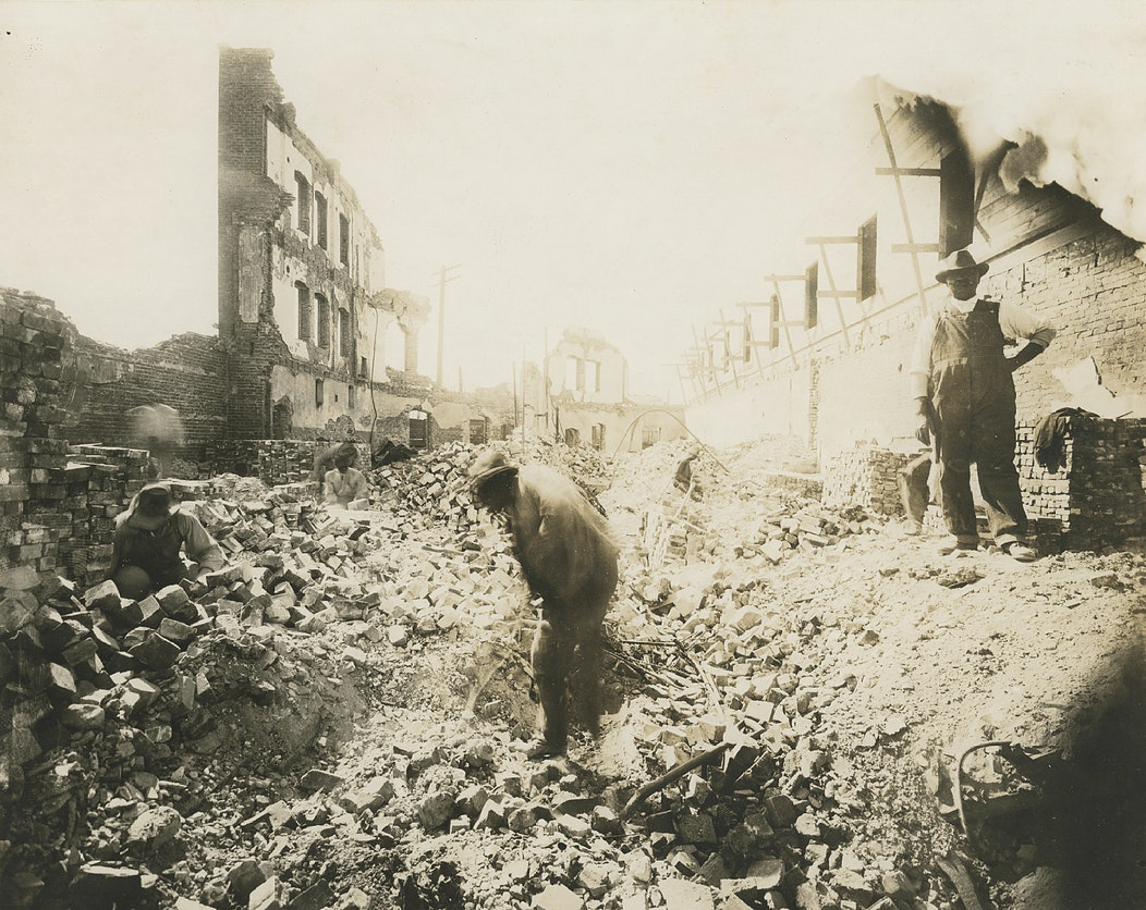 Photograph of four men digging in fallen and burned building