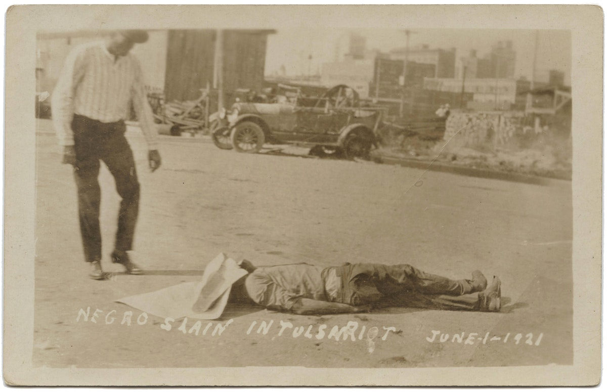 A white man stands over a dead person covered in the street